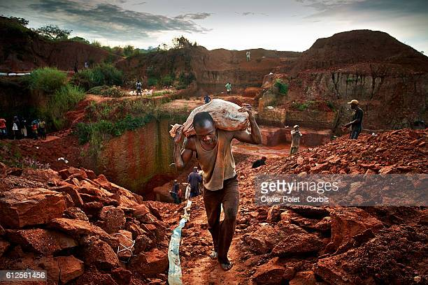 Miner carries bags filled with excess earth 28 March 2013 to clear the concession and expose the diamondrich layers near an Angolan village not far...