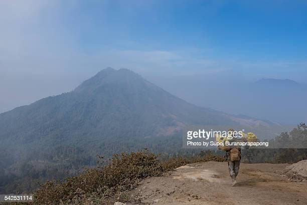 Miner carries sulfur up rocky volcano path