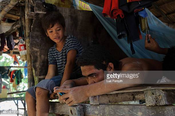 A miner checks his cell phone during the midday break from work on April 22 2014 in PinutAn Philippines Gold mining is the primary source of income...