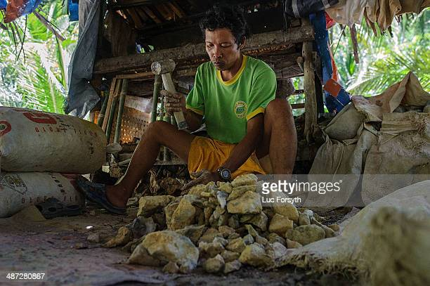 A miner crushes rock fragments into smaller more manageable pieces using a sledgehammer and an anvil stone on April 22 2014 in PinutAn Philippines...