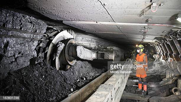 miner cutting coal at coal seem in deep mine - coal mining stock photos and pictures