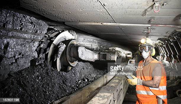 Miner cutting coal at coalface in deep mine