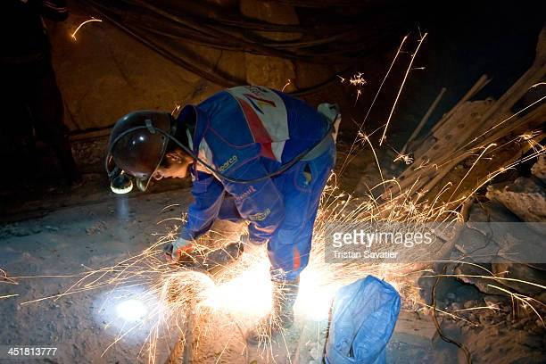 Miner cutting trolley rails to divert them toward another mine tunnel, in the old Candelaria silver mine in Potosi . Potosi is one of the highest...