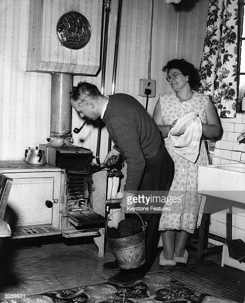 Miner Frankie Vaughan of the Swadlingcote Colliery Derbyshire stokes the stove at his home with coal while his wife Betty looks on Frankie won the...