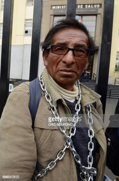 A miner from near Pasco Peru remains chained to the fence of the building of the Ministry of Health in Lima during a protest in demand of government...