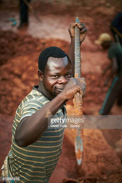 A miner glances at the photographer as he uses an iron bar to break the diamond carrying earth layer 28 March 2013 at the 7/7 diamond mining site...