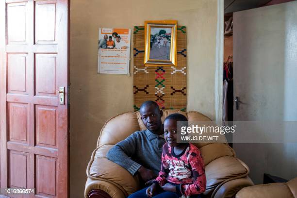 Miner Gugu Malatsa retrenched by Evander Gold mine and rehired as a contract worker poses with his 8yearold son Somi in Evander on June 14 2018 At...
