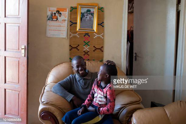 Miner Gugu Malatsa retrenched by Evander Gold mine and rehired as a contract worker shares a laugh with his 8yearold son Somi as they pose in Evander...