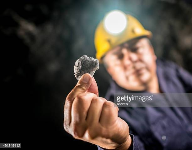 Miner holding a piece of rock at the mine