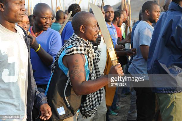 A miner holds up a machete as he takes part in a strike calling for increased wages at a platinum mine in Marikana on August 16 2012 An illegal...