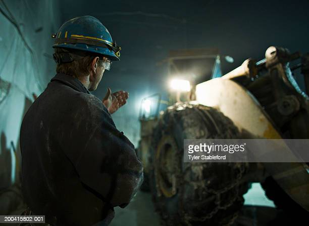 Miner in hardhat signalling to bucket loader in marble quarry