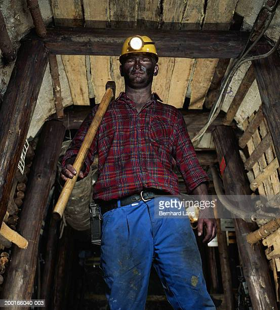 Miner in mine shaft carrying pickaxe, low angle view, portrait