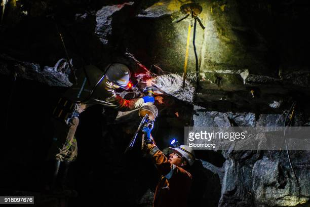 A miner inserts steel reinforcement rods into the rock face inside a mine shaft at the Northam Platinum Ltd Booysendal platinum mine located outside...