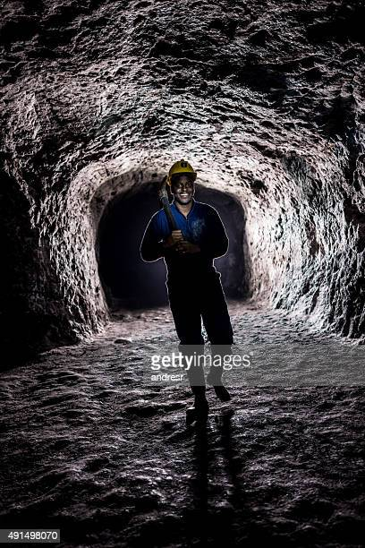 Miner inside a dark tunnel at a mine