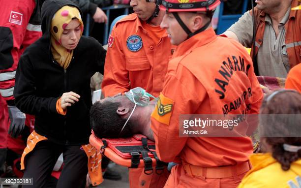 Miner is carried to an ambulance as his relative looks concerned on May 14, 2014 in Soma, Turkey. Rescuers pulled more dead and injured from the coal...
