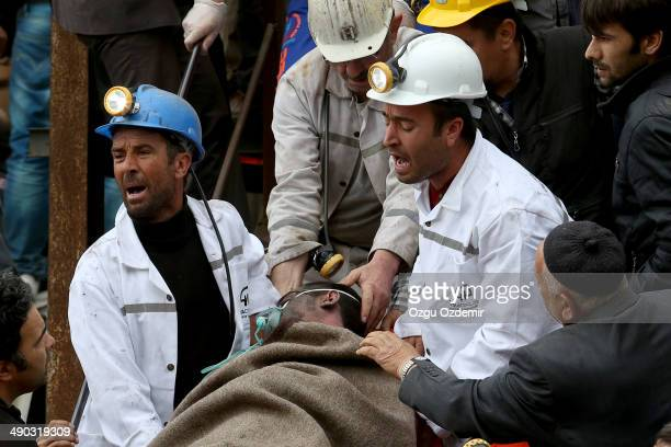 Miner is helped by rescue workers from the coal mine on May 14, 2014 in Soma, Manisa, Turkey. An explosion and fire in the coal mine killed at least...