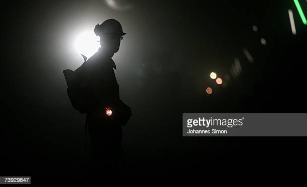 A miner is silhouetted against a floodlight at the construction site for the Gotthard Base Tunnel on April 19 2007 near Sedrun Switzerland Deep...