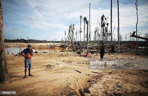 A miner looks on as National Police officers search for illegal mining operations in a deforested section of the Amazon lowlands ravaged by mining on...