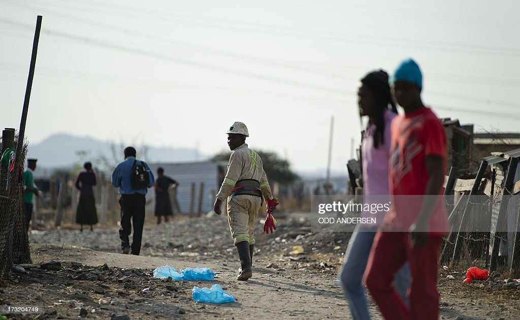A miner (C) makes his way home after work on July 9, 2013 in the Nkaneng shantytown next to the platinum mine, run by British company Lonmin, in Marikana. On August 16, 2012, police at the Marikana mine open fire on striking workers, killing 34 and injuring 78, during a strike was for better wages and living conditions. Miners still live in dire conditions despite a small wage increase.