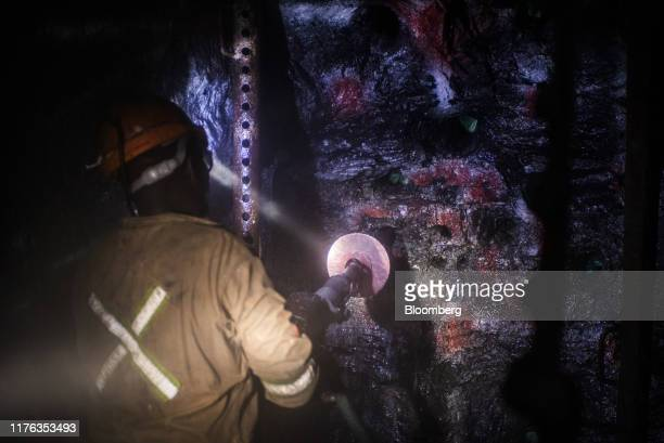 A miner operates drilling machinery in the mine shaft during a media tour of the SibanyeStillwater Khuseleka platinum mine operated by Sibanye Gold...
