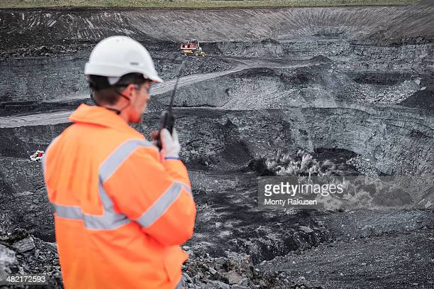 Miner overseeing blasting explosion in surface coal mine