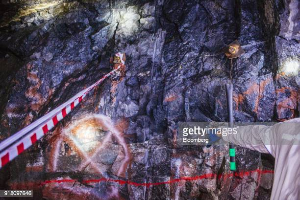A miner points towards the Upper Group 2 Reef platinum rich rock layer in the Northam Platinum Ltd Booysendal platinum mine located outside the town...