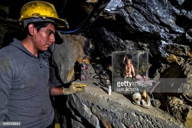 TOPSHOT A miner prays for San Sebastian before descending to work at 100 m depth at 'La Corte' gold mine in La Llanada Narino department on October...