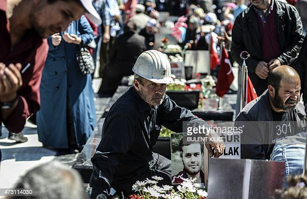 Miner sits at by a grave as relatives and friends gather at the cemetery in the Turkish town of Soma in the Manisa district, western Turkey, on May...