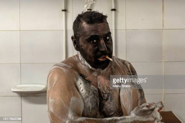 Miner smokes a cigar while showering at the end of his workday on May 10, 2021 in Mieres, Spain. The San Nicolas mine in Spain's northern region of...