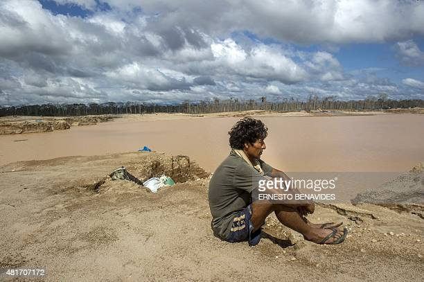 A miner stands by during the police interdiction of an illegal gold mining area of La Pampa in Madre de Dios southern Peruvian jungle on July 14 2015...