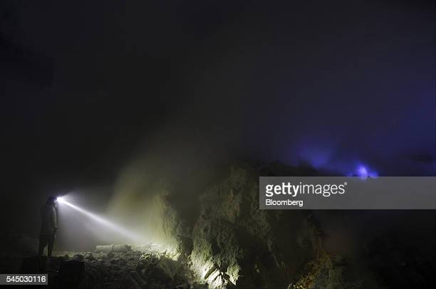 A miner stands with a head torch as ignited sulfuric gas known as blue fire or blue frame rises from the Ijen volcano at night in Banyuwangi East...