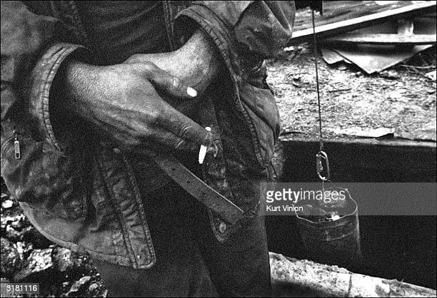 A miner takes a break as coal is hauled out of a mineshaft in a bucket February 25 2002 near Snezhnoye Ukraine A 100pound sack of coal can...