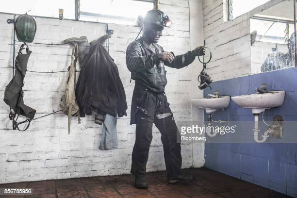 A miner takes off equipment after a work shift at a coal mine in Cucunuba Cundinamarca Department Colombia on Friday July 28 2017 Colombia is set to...