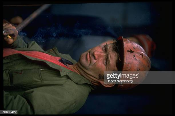 Miner taking cigarette smoking break at 1 of largest open pit coal mines in world extracting 200000 tons day in Central Steppes region Ekibastuz