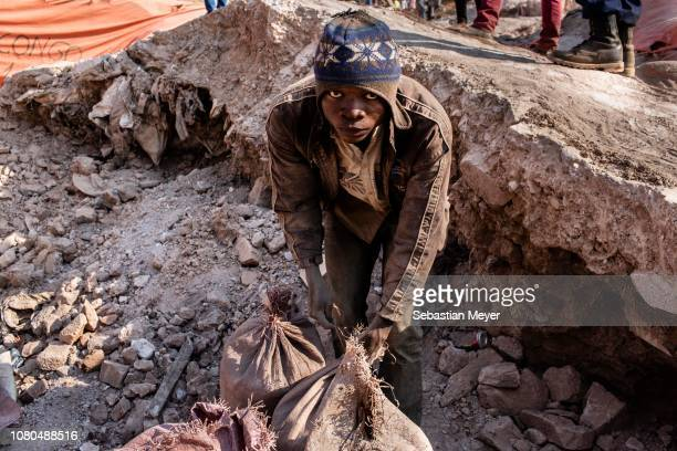 """Miner toes together bags of cobalt inside the CDM Kasulo mine. """"n""""nCobalt is a vital mineral needed for the production of rechargeable batteries. Two..."""