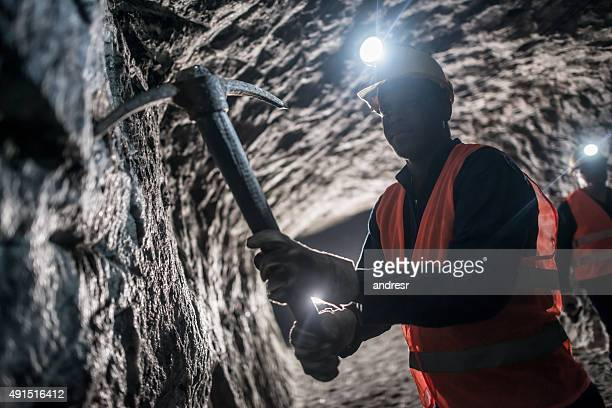 miner using a pick tool at the mine - underground mining stock photos and pictures
