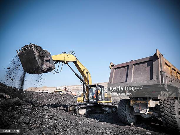 Miner using digger to lift coal from opencast coalmine into dumper truck