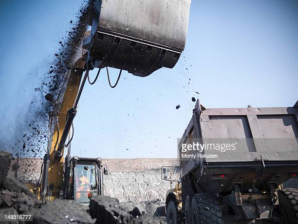 Miner using digger to lift coal from opencast coalmine