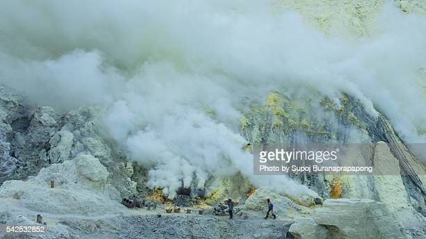 a miner walking around in kawah ijen indonesia - acid warning stock photos and pictures