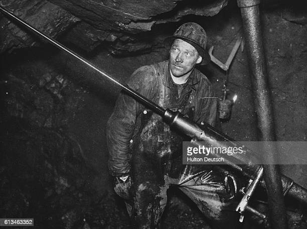 A miner wearing a protective hard hat looks upwards while he works the automatic drilling machine