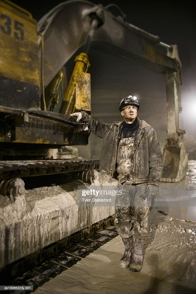 Miner with hardhat and headlamp standing next to earth mover : Foto stock