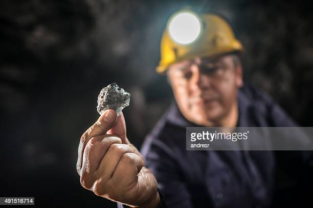 Miner working and holding a piece of rock