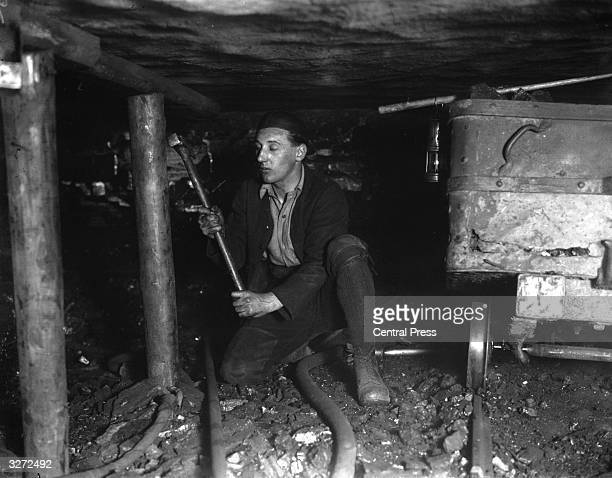 Miner working underground at Ashington colliery fixing pit props.
