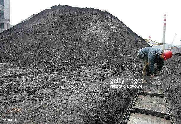 A miner works repairing tracks for transporting coal at a mine in Huangling county north of Xian 25 May 2005 in western China's Shaanxi province...