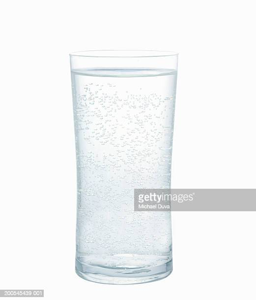Mineral water in glass against white background, close-up