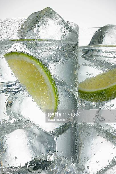 mineral water with lime wedges - soda bottle stock photos and pictures