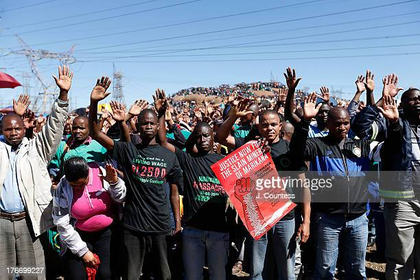 Miners and supporters of the Marikana mining community pray during a memorial service to commiserate the one year anniversary of the massacre at...