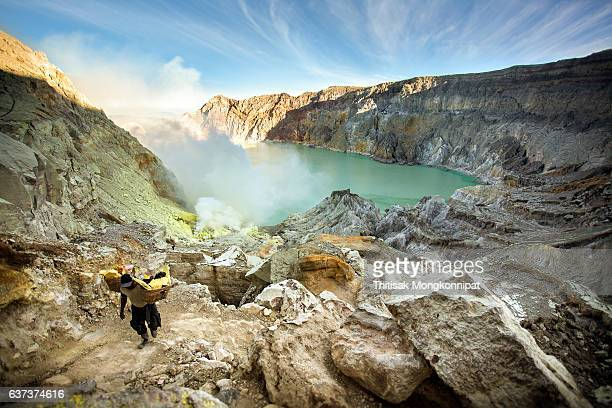 miners are carrying sulfur from ijen volcano blue flames - acid warning stock photos and pictures