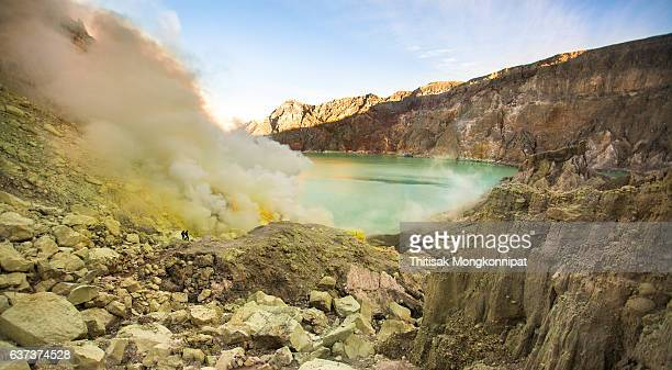 miners are carrying sulfur from ijen volcano - acid warning stock photos and pictures