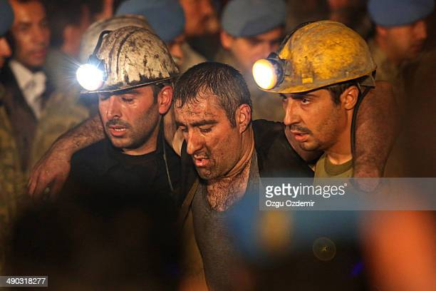 Miners are helped by rescue workers and friends from the coal mine on May 14, 2014 in Soma, Manisa, Turkey. An explosion and fire in the coal mine...